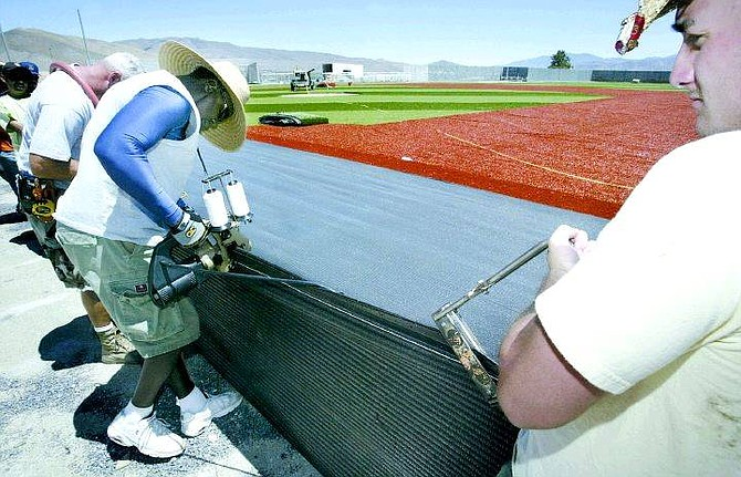 Cathleen Allison/Nevada Appeal  Members of a crew from Field Turf Builders install turf on the baseball field at Western Nevada Community College Thursday. Desmond Cooper, left, stitches together two pieces of turf while Casey SImpson, right, helps keep tension on the turf. The crew is installing nearly 128,000 square feet of turf and expect to be finished by the end of next week.