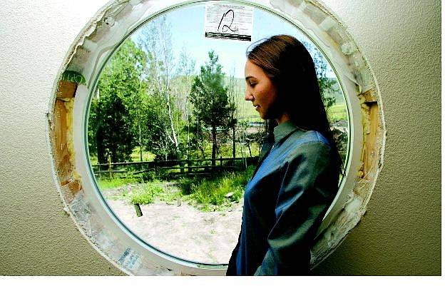 BRAD HORN/Nevada Appeal Amanda Carlson poses in the window she designed for her family's Kings Canyon home on Thursday. The Carlson's lost their home to the Waterfall fire last summer.
