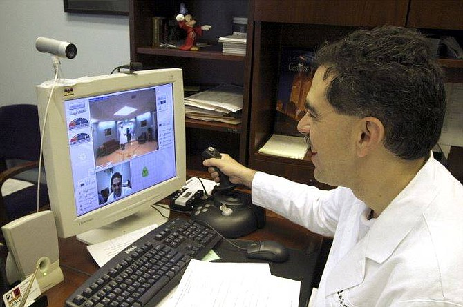 """Urologist Louis Kavoussi makes his morning rounds while sitting in his Johns Hopkins Hospital office in Baltimore. Skeptics fear this and other new """"telemedicine"""" technologies are depersonalizing health care and eroding what remains of the doctor-patient relationship. Illustrates HEALTH-ROBOTS (category l), by Rob Stein © 2005, The Washington Post. Moved Wednesday, July 6, 2005. (MUST CREDIT: Washington Post photo by Sarah L. Voisin.)"""
