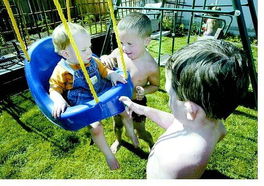 Cathleen Allison/Nevada Appeal Josh Morris, 4, center, swings his little brother, Joey Morris, 1, in their back yard Wednesday with their cousin Danny Cecil, 4. Joey was born during the Waterfall fire last year.