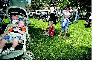Brad Horn/Nevada Appeal Graeme Eckery, 2, in front of stroller, and his twin brother, Brock, of Carson City,  take a nap at Fuji Park while Colin Ellsworth, 5, and his sister Lauren, 3, of Vacaville, Calif., look at Vintage motorcycles with their father during the 10th annual British-European Vintage Motorcycle Show and Swap on Saturday.