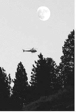 Chad Lundquist/Nevada Appeal A firefighting helicopter flies past the nearly full moon Monday evening over the Genoa blaze area.