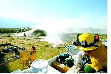 Belinda Grant/Nevada Appeal News Service Becky Bopko, a volunteer with the Sheridan Fire Department, sprays the Deck gun onto the hay bale fire. The fire was at the Thunderbird Ranch, owned by Jessica Ledbetter, on Dressler Lane off Highway 88. Approximately 200 bales of hay burned -  they were put up just eight days ago.