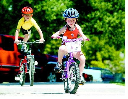 BRAD HORN/Nevada Appeal Autumn Keith, 5, trains for the upcoming triathalon at Mills Park while her brother Josh, 8, performs a seat stand on Wednesday. Caleb, 10, the Keith's oldest child, will also compete in next month's event.