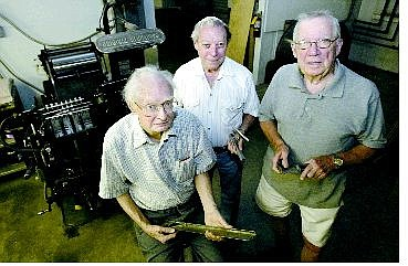 From left, Bill Dolan, Greg Krem and Sam Bauman combine for 169 years of journalism. They posed at Sierra Nevada Printing Friday afternoon in front of a more than 50-year-old Heidelberg press.   Cathleen Allison/Nevada Appeal