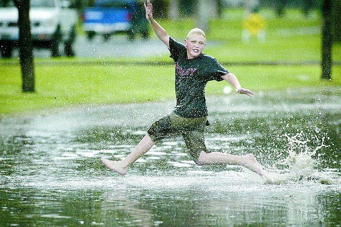 Cathleen Allison/Nevada Appeal Gavin Knight, 11, plays in the rain as Thursday afternoon thunder showers brought several feet of runoff through Mills Park.