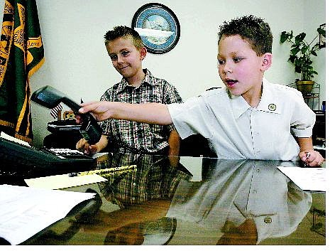 Chad Lundquist/Nevada Appeal Ernrique Sanchez, 8, of Carson City makes executive decisions as he learns about what it takes to be sheriff for a day. His brother Kaleb VanMeter, 7, left, helps with those issues as the official undersheriff.