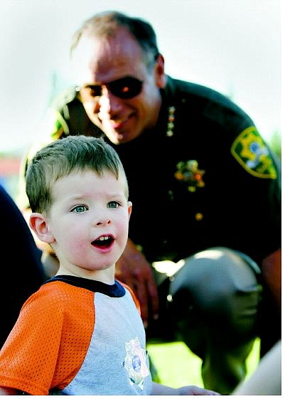 Chad Lundquist/Nevada Appeal Sheriff Kenny Furlong talks to Grant Kuhlmann, 3, of Carson City at the Sheriff's Department's National Night Out picnic Tuesday evening in Mills Park.