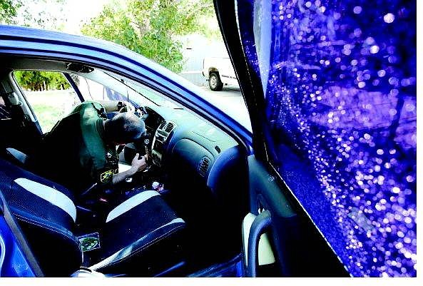 Chad Lundquist/Nevada Appeal Carson City Sheriff's Deputy Brian Hardy searches the steering column of this Mazda Protege for the .22 cal. bullet that passed through its passenger window on Tuesday night. It was one in a string of shootings in the late-night and early morning hours.