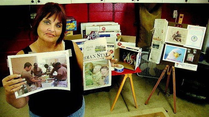 Kevin Clifford/Nevada Appeal P.J. Degross of Carson City stands in front of her Web of Support work station Thursday in her garage where she ships goods to deployed soldiers of the Mississippi National Guard. She holds a picture of soldiers receiving the packages she sent and a newspaper article about Sgt. Norris Galatas, who asked her to help his men after being injured.