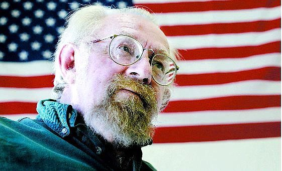 Chad Lundquist/Nevada Appeal John Clark, 60, a homeless Carson City man, poses in front of an American flag hanging of the wall of the Friends in Service Helping building for Monday's point-in-time count. This was the second count held by FISH this year.