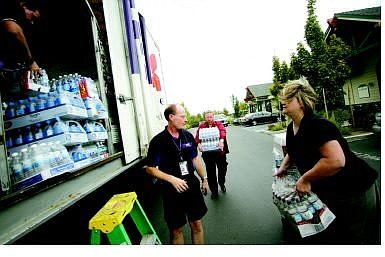 BRAD HORN/Nevada Appeal Irwin Union Bank vice president Bill Fergus, center, carries two cases of water to the Federal Express truck while Janette Jones helps Gregg Berggren, operations manager, and Dave Waldrip, a courier, load the donated water Thursday. Berggren said that Federal Express has delivered more than 200 tons of supplies including one DC-10 airliner filled with cots that were sent to the Houston Astrodome.