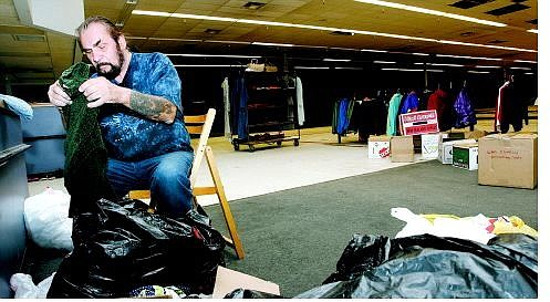 Chad Lundquist/Nevada Appeal Charlie Palecki, of Silver Springs, a volunteer, sorts through bags of clothing on Monday for the Katrinas Hope a grassroots relief group that is collecting donations at the old Wal-Mart in Carson City.