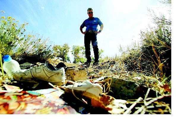 BRAD HORN/Nevada Appeal Ron Bowman, co-chairman of the Carson City Kiwanis Club, stands in the remains of a trailer that was torched near the Carson River on Thursday. The Kiwanis will hold its 20th annual river cleanup Oct. 8.