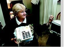 Chad Lundquist/Nevada Appeal Judy Harris, RSVP field representative, holds one of the LifeLine buttons at her home in Dayton on Wednesday afternoon. Lifelines are communications devices for the elderly to use when they can't get to a telephone