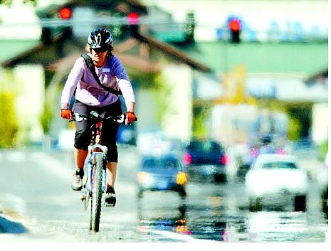 BRAD HORN/Nevada Appeal Anne Macquarie rides her bike from Albertsons on North Carson Street to her office on College Parkway on Friday. Instead of driving her car, Macquarie will ride her bike and take public transportation this month.