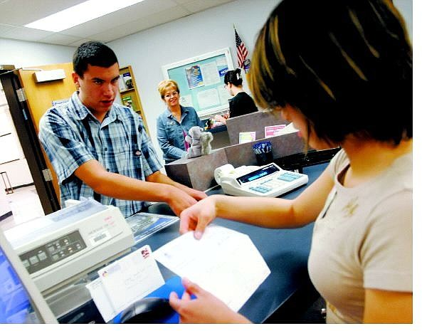 Brian Sokol/Nevada Appeal Sophomore Adam Wungnema, 15, makes a transaction with Student Teller Jenny Lau, 17, at the Nevada Credit Union's Educational Branch in Carson High School on Friday.