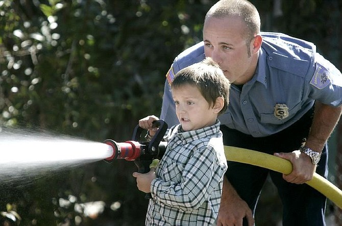 Cathleen Allison/Nevada Appeal Carson City firefighter Brad Mihelic helps Garrett Watkins, 5, spray a fire hose Wednesday at Station No. 1 as part of the Firehouse Experience. Students from Fritsch Elementary School were part of some 700 Carson City children who will visit the fire station during October, which is Fire Prevention Month.