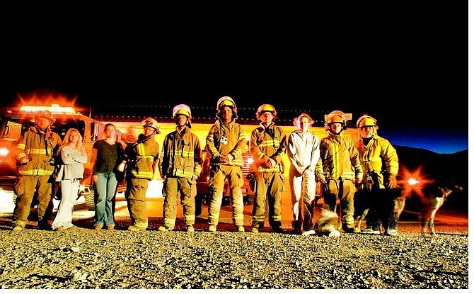 BRAD HORN/Nevada Appeal Silver City volunteer firefighters and their families stand in front of the station on Monday evening. Pictured from left are Fire Chief Kip Allander, his sister and firefighter Patricia Allander; support member Sarah and Assistant Fire Chief Grahame Ross with their 10-month-old son, Liam; firefighters Erik Fernquest, Josh Niblett, Zac Pederson; support member Anna Brown; firefighters Thaddeus Coughran, Larry Steinberg and dogs Lex and Cosmo.