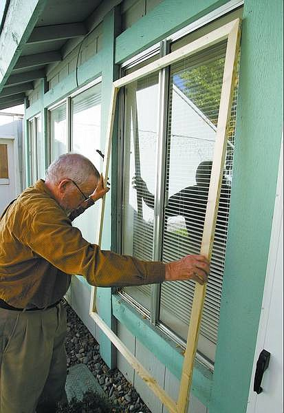 Cathleen Allison/Nevada Appeal Sam Bauman checks the size of a storm window at his home Thursday afternoon.