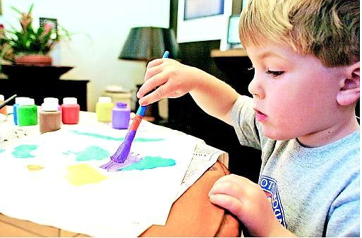 Noah Lyle, 3, paints a fish that will be sold on eBay. Noah has received offers to appear on local and national talk shows.  Julie Sullivan/  Appeal News Service