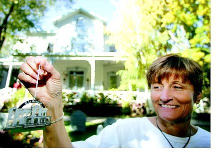 BRAD HORN/Nevada Appeal Sue Jones, co-owner of the Purple Avocado, displays the Carson City Christmas Ornament in front of the Bliss Mansion on Thursday. The piece is the fourth installment in a collection of 12 ornaments and will go on sale Saturday.