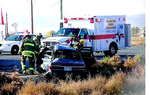 Photo by Mike Moore/For the Nevada Appeal Lyon County rescue crews work to free a 17-year-old girl trapped in her vehicle following a collision Thursday morning at Occidental Drive and Highway 50. This was the second time in a week when a 17-year-old was injured trying to pull out from the River Park subdivision, a new development of more than 500 homes in Dayton.