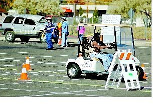 BRAD HORN/Nevada Appeal Katie Carlevato, 14, drives a golf cart through an obstacle course wearing drunk goggles, while her friend Amanda Wong, 13, enjoys the ride during the Community Awareness Fair at Carson High School on Saturday. The vehicle in back shows what happens when people drive while impaired by alcohol.