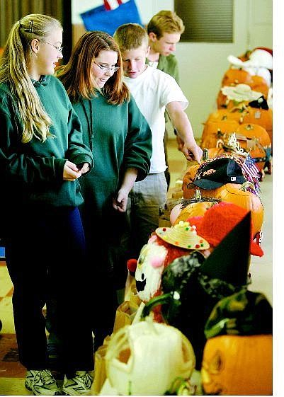 St. Teresa students, from left, Kelly Johnson, Kristin Stanford, Dominic Cavilia and Shaun Fitzgerald, all 14, vote for their favorite in a pumpkin-decorating contest Oct. 14 at the school. Approximately 70 students participated in the contest.