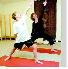 Shannon Litz/Appeal News Service Yoga instructor Jill Mustacchio does a yoga position with her son Jaden, 10, at O2 Wellness Studio. Mustacchio will be teaching a yoga for cancer patients class as well as a yoga for kids class.
