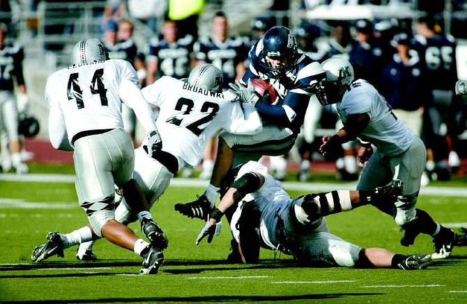 Nevada receiver Jack Darlington gets tackled by Hawaii defenders, from left, Adam Leonard (44), Lamar Broadway (22), Melila Purcell (98), and Lono Manners (15) in the second half of Saturday's game, Nov. 5, 2005 in Reno, Nev. Nevada won 38-28. (AP Photo/Cathleen Allison)