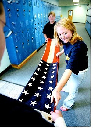 Cathleen Allison/Nevada Appeal Carson Middle School eighth-graders, clockwise from front, Robyn Gowan, Alyssa Brown and Shayna Ruybalidi, all 13, practice folding an American flag in preparation for Thursday's Veterans Day Commemoration program honoring former area military personnel.