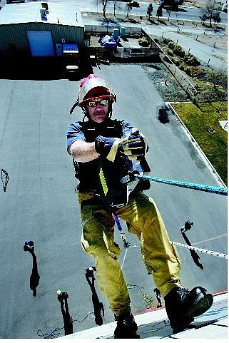 Chad Lundquist/Nevada Appeal Carson City Fire Department Training Captain Jim Quilici, 45, scales the side of the training tower Wednesday with the help of a PowerQuick personal lifting system. The Discovery Channel filmed the exercise.