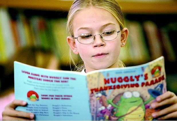 Cathleen Allison/Nevada Appeal Hugh Gallagher Elementary fourth-grader Jennifer Burns, 9, reads through books available through the school's Reading is Fundamental program. Students in every grade receive one free book when the school sponsors the event.