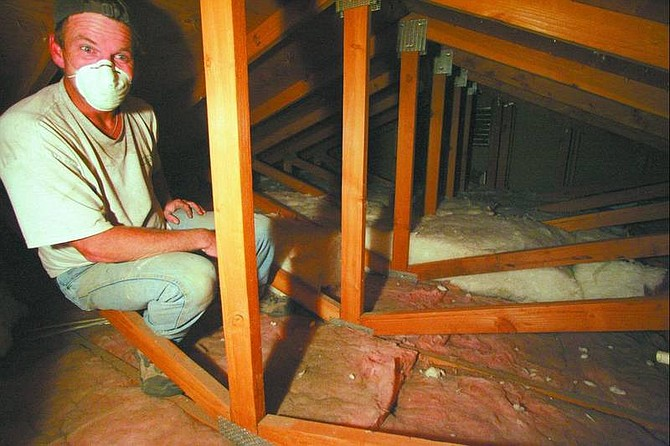 BRAD HORN/Nevada Appeal Todd McPhail installs thicker insulation material into the attic of a north Carson City home. The insulation will help keep the home warm in the winter and cool in the summer.