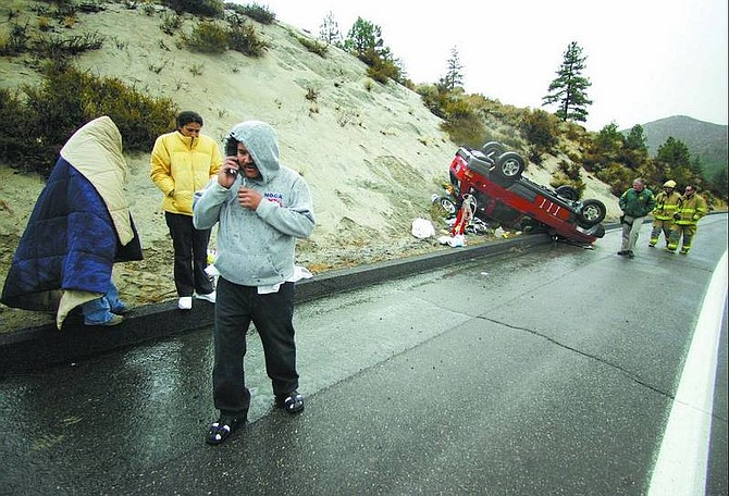 BRAD HORN/Nevada Appeal Rafael Infante talks on his phone while Karina Garcia, back left, and Eva Estrada, who were involved in a rollover accident at the base of Spooner Summit, try to stay dry in the rain Friday morning.