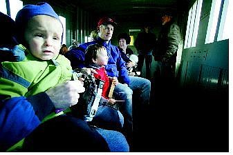 BRAD HORN/Nevada Appeal Gabriel Bonicatto, 2, of Reno, enjoys his first train ride at the Nevada State Railroad Museum on Saturday. Pictured center to back are Camdyn, 3, and his father Scott Meikrantz, of Carson, and Shirley Costarella, of San Jose, Calif. Free train rides were given in exchange a donation to the Toys for Tots program.
