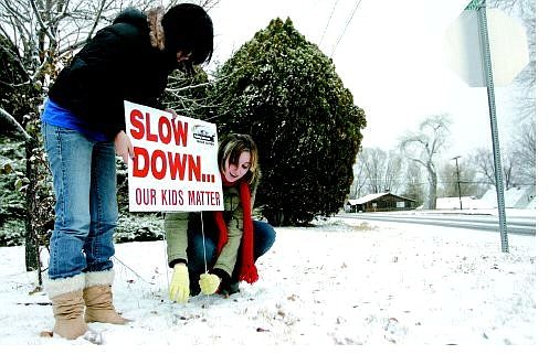 Chad Lundquist/Nevada Appeal Carson High School students Alejandra Melgarejo, left, and Lydia Peri erect a Project Ignition sign asking drivers to slow down Monday afternoon at the corner of Division and Fleischmann. Twenty signs will be erected along highly traveled roads in Carson City.