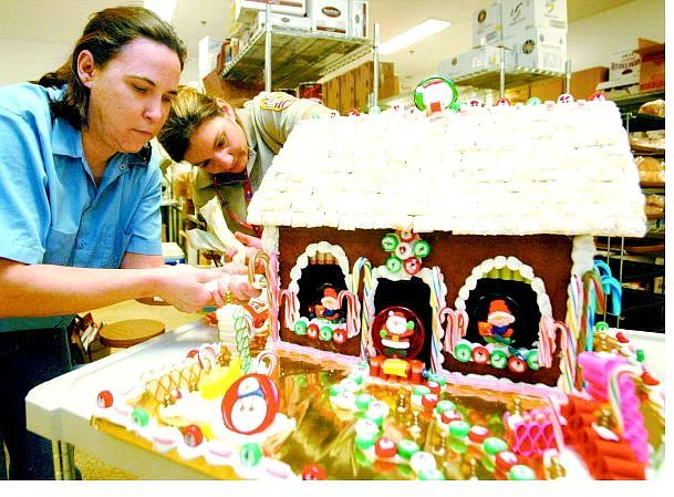Belinda Grant/Nevada Appeal News Service Douglas County Jail trusty Rosalie Benvin, left, and Douglas County Jail cook Andrea Lombard put finishing touches on the jail's gingerbread house entry for a contest sponsored by the Carson Valley Arts Council.