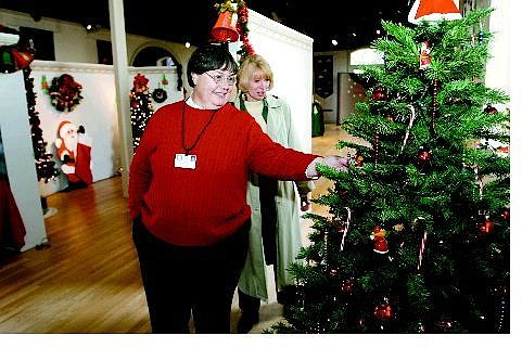 Cathleen Allison/Nevada Appeal Phyllis Sargent, left, and Jan Leuvano look at the Festival of Trees display at the Nevada State Library and Archives Wednesday. Twenty-five holiday craft items are being auctioned off to support the museum's gallery program.