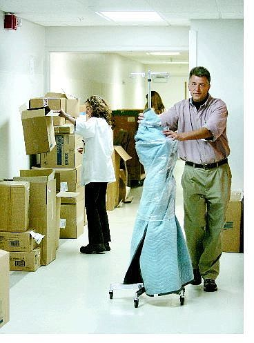 Cathleen Allison/Nevada Appeal Carson-Tahoe Hospital employees sort through empty boxes as Frank Martin of Graebel Companies moves equipment to a truck to be taken to the new Carson Tahoe Regional Medical Center on Thursday afternoon. Patients will be moved to the medical center Saturday.