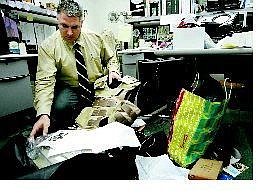Cathleen Allison/Nevada Appeal Carson City Sheriff's Detective Dave LeGros looks through some of the items allegedly purchased by two men with money they reportedly stole from a Buzzy's Ranch Road home.