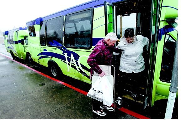 Chad Lundquist/Nevada Appeal Ray Soloninka, 79, helps his wife, Barbara, 64, step off of a JAC bus at the Plaza Street transfer station on Nov. 28. Officials say bad weather and no bus shelters are keeping ridership numbers down during the system's first paid month of operation.