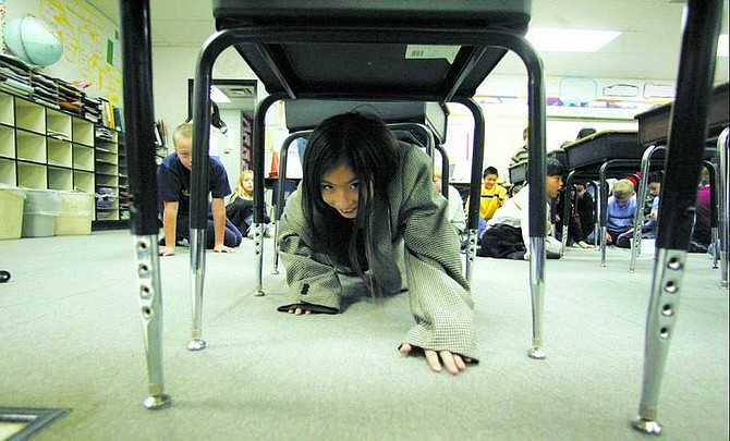 BRAD HORN/Nevada Appeal Elizabeth Bracamontes, 9, crawls through a mock subway at Fremont Elementary School on Friday.