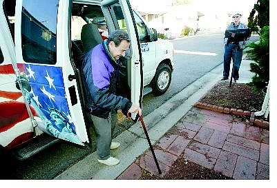 Cathleen Allison/Nevada Appeal Disabled American Veteran van driver George Egbert, right, watches as Stan Kessler disembarks at his home Thursday afternoon. Veterans, who ride the van to and from medical appointments in Reno, face new restrictions.