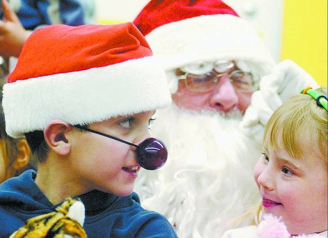 BRAD HORN/Nevada Appeal Tyler Roberts, 10, and Brianna Stark, 7, sits on Santa's lap during their party at Seeliger Elementary School.