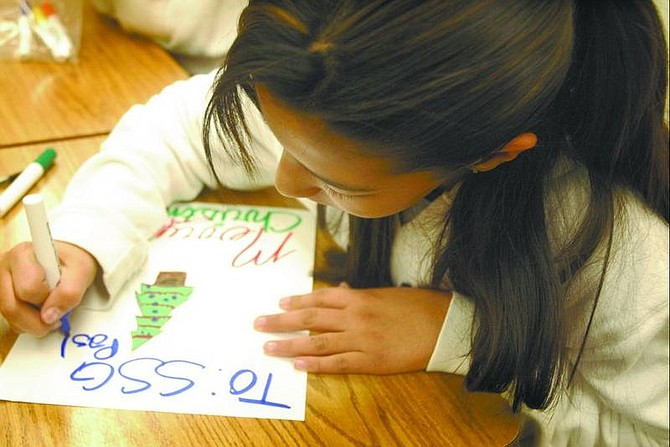 """Kevin Clifford/Nevada Appeal Sixth-grader Bianca Carrasco, 11, of Eagle Valley Middle School makes a Christmas card for Staff Sgt. Joseph Pastorek in Afghanistan. The class is participating in the Army's """"Operation Giving Thanks."""""""
