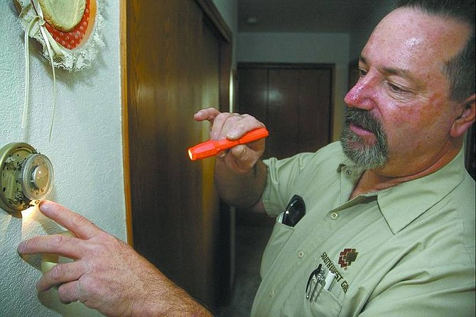 Kevin Clifford/Nevada Appeal Mark Della, customer service technician for Southwest Gas Corp., checks the thermostat for efficiency Friday morning in Carson City.