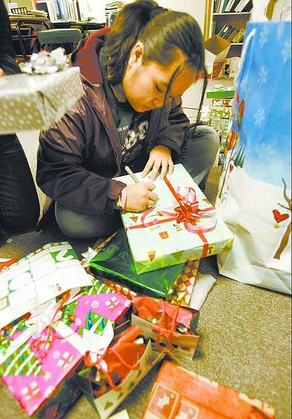 Cathleen Allison/Nevada Appeal Christy Lin, 16, puts tags on some of the gifts Carson High School Advanced Placement English students donated for a family they adopted for Christmas. Students raised money or donated gifts for the Carson City family of five.