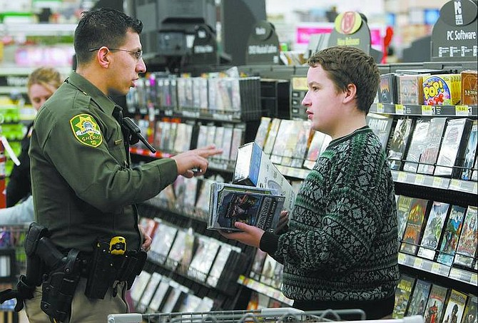Cathleen Allison/Nevada Appeal Carson City Sheriff's Deputy Dan Gonzales helps James Jarrard, 13, calculate his gifts while shopping at Wal-Mart Monday morning. Volunteers helped area middle school students spend  $50 gift cards.
